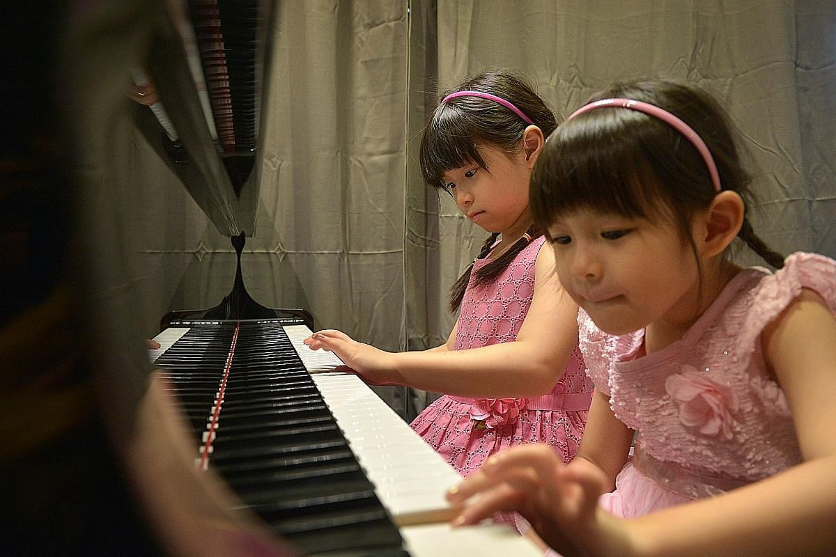 Ethan Sam (seated) took up the piano after his elder brother, Elston, did not sit the ABRSM Grade 7 piano examination, for which his mother, Ms Regine Wong, had already paid the registration fees. Above: Vivienne Lee and her younger sister, Charmaine