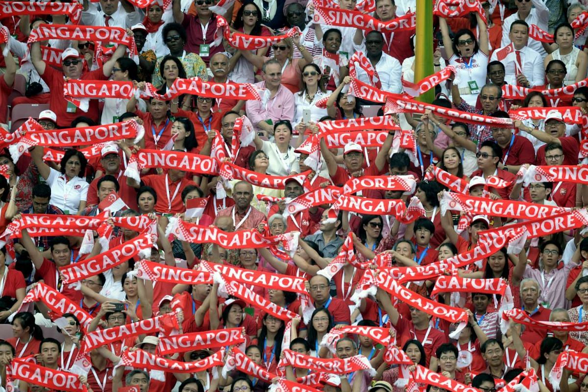 Spectators holding up a Singapore banner during the SG50 National Day Parade at the Padang on Aug 9, 2015.