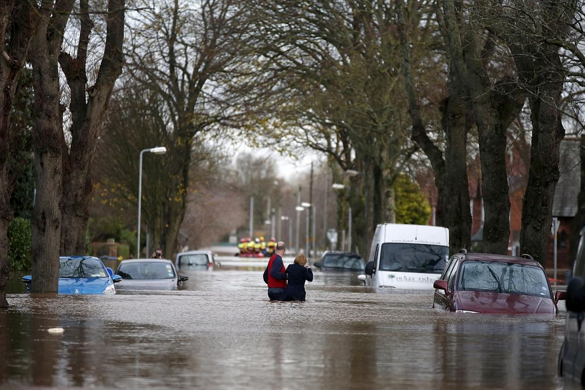Residents wade through flood waters in the Warwick Road area of Carlisle, Britain on Dec 6, 2015.