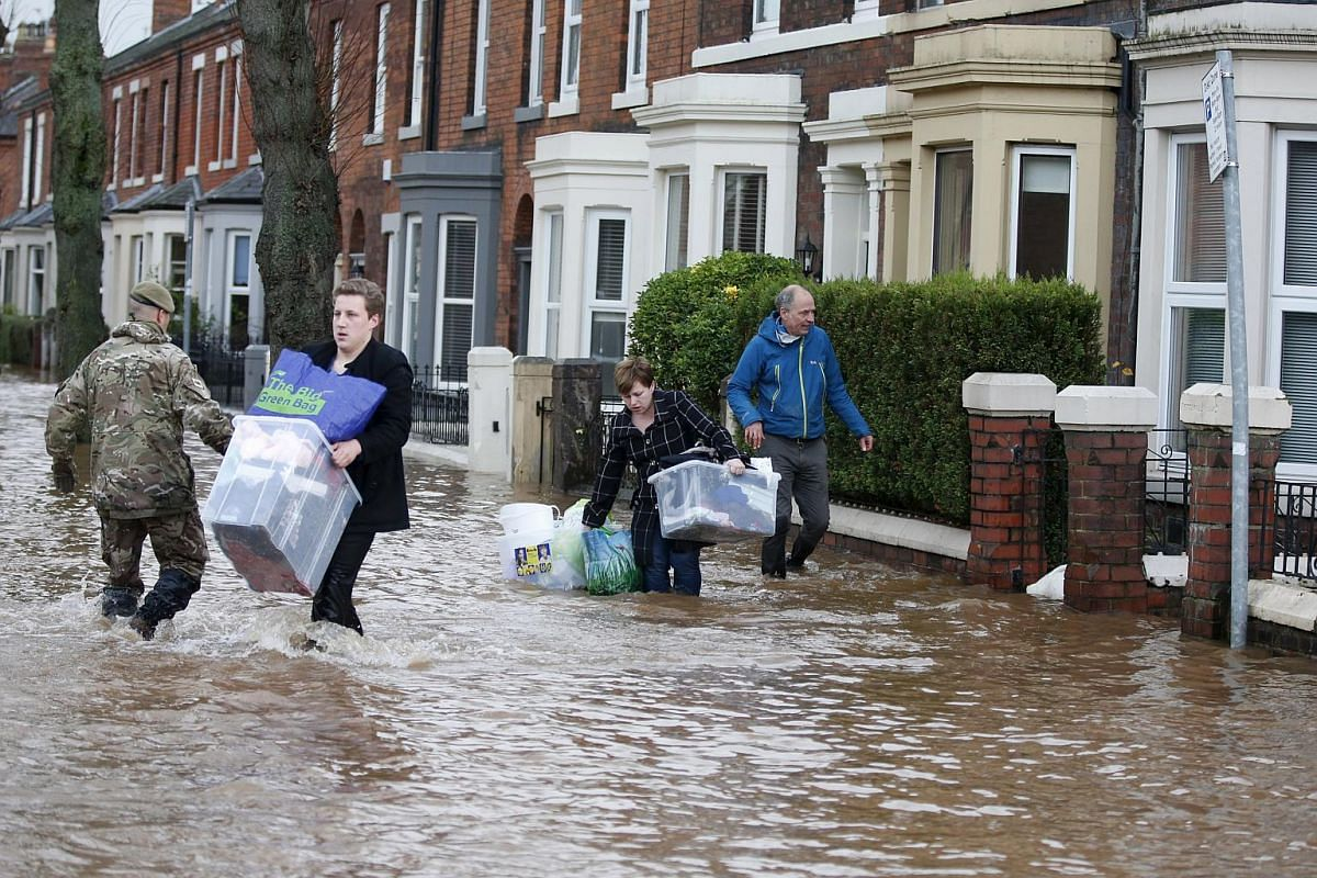 Residents carry their belongings through flood waters in the Warwick Road area of Carlisle, Britain on Dec 6, 2015.