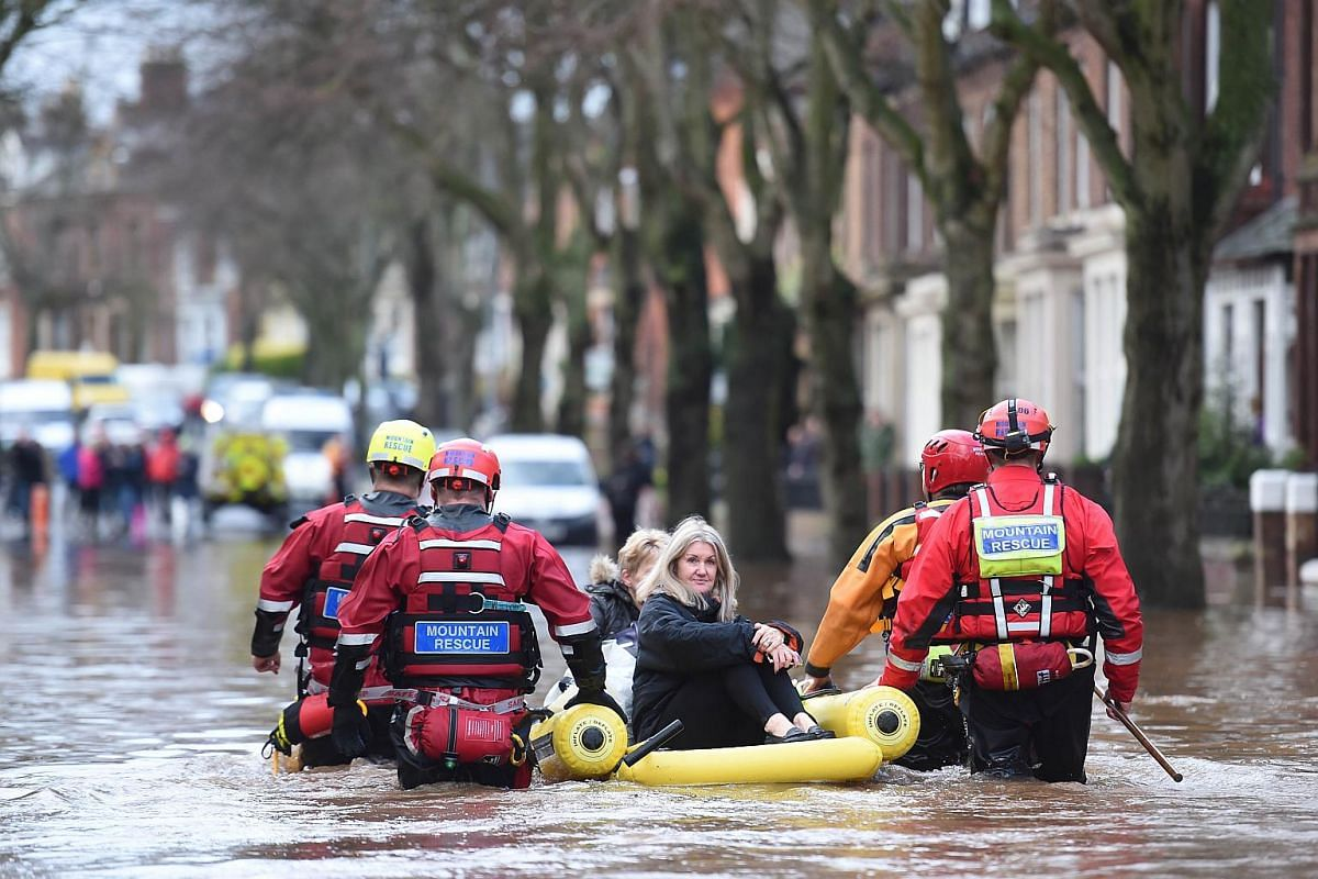 Members of the emergency services move stranded people from a flooded street in Carlisle on Dec 6, 2015.