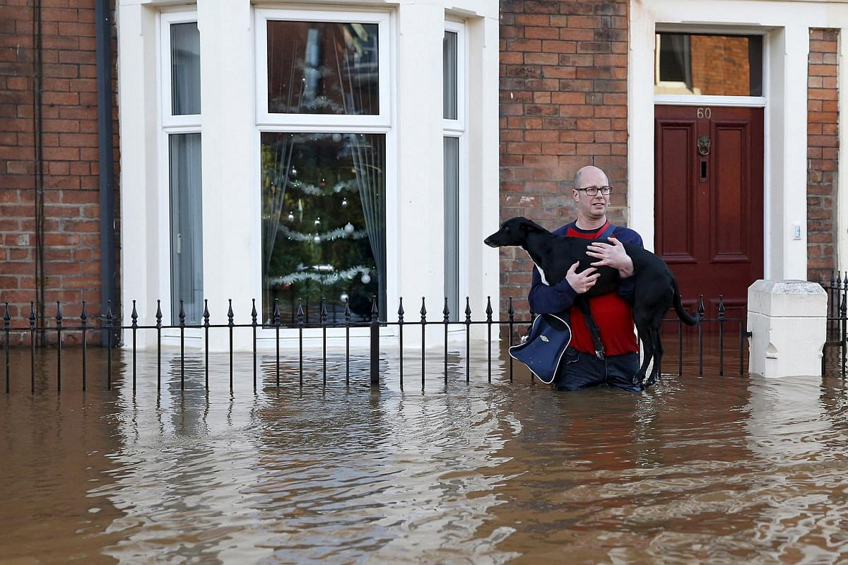A man holds his dog as he wades through a flooded residential street in Carlisle, Britain Dec 6, 2015.