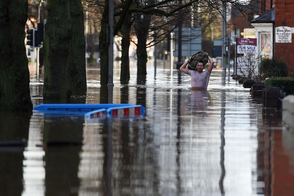 A man carries his back above his head as he wades through a flooded street in Carlisle, northern England, on Dec 6, 2015.