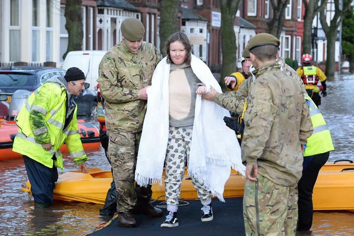 Picture made available by the British Ministry of Defence shows British soldiers from 1st Battalion, The Duke of Lancaster's Regiment, assisting in evacuating residents, North West England, Britain, on Dec 6, 2015.