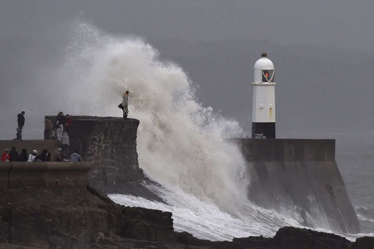A man and a child stand on the harbour wall during stormy conditions at Porthcawl, South Wales, on Dec 6, 2015.