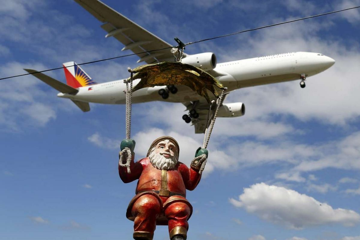 A Philippines Airlines (PAL) plane flies over a Santa Claus doll hanging at a home (unseen) in Manila, the Philippines, on Dec 7, 2015.
