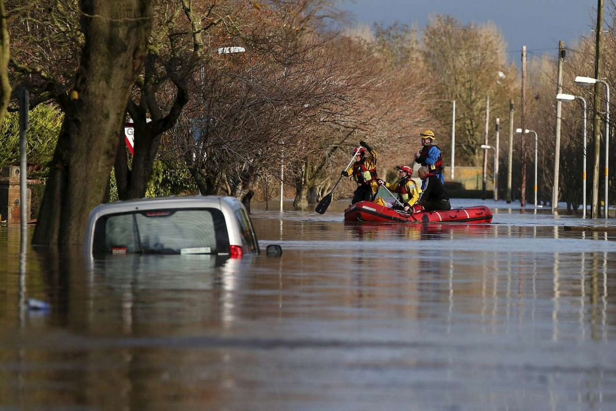 Rescue workers evacuating local residents by boat from a flooded residential street in Carlisle, Britain, on Dec 6, 2015.