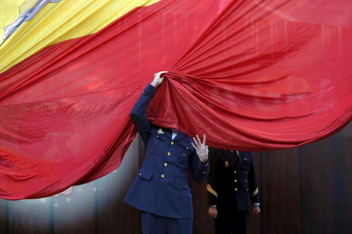 A member of the Spanish Armed Forces gets his face covered by a giant Spanish flag while helping to raise it during a ceremony to mark the 37th anniversary of the 1978 Spanish Constitution in Madrid, Spain, on Dec 6, 2015.
