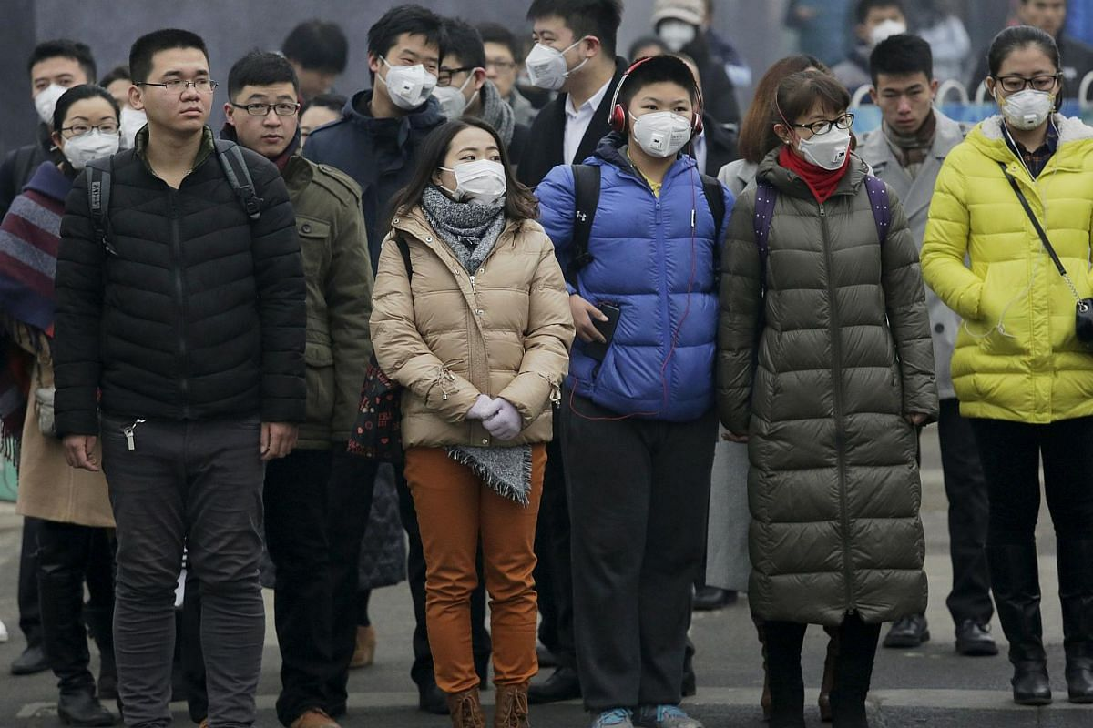 "Commuters wearing protective masks as protection from the extreme smog in central Beijing on Dec 8, 2015, as China's capital issues its first ever ""red alert"" for pollution."