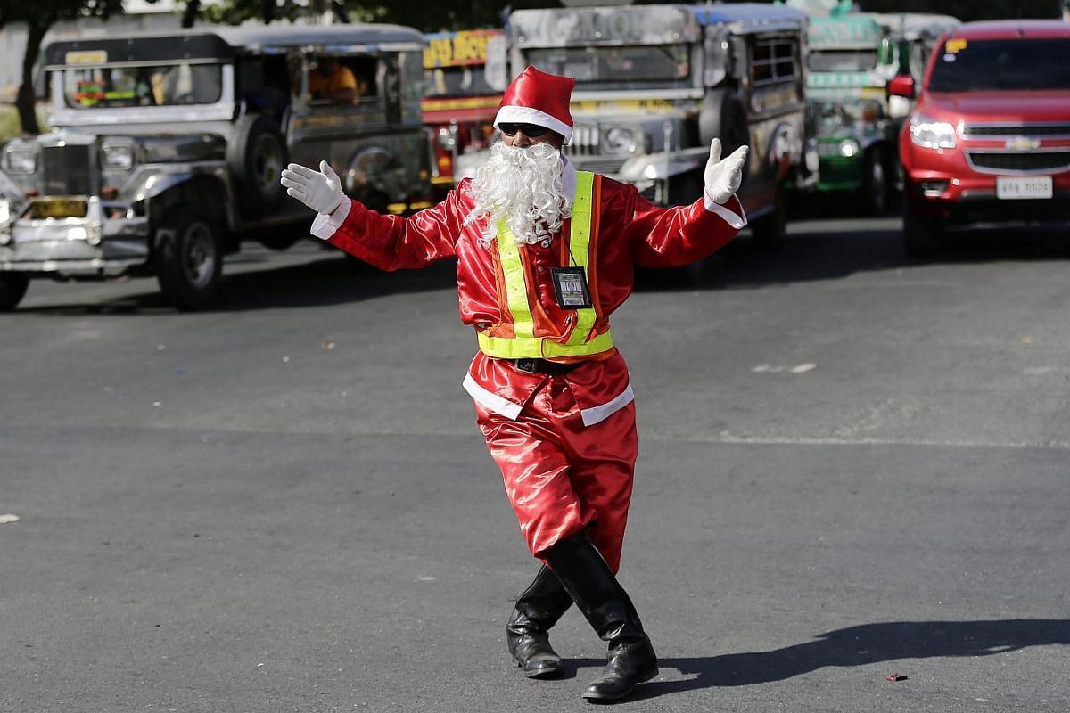Dressed  in a Santa Claus costume, Filipino traffic enforcer Ramiro Hinojas directs motorists on a street in Pasay city, south of Manila, in the Philippines, on Dec 8, 2015.