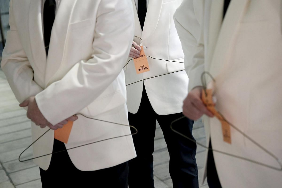 Uniformed attendants holding hangers to check coats for guests arriving for the An Evening Honoring Valentino gala benefiting the Lincoln Center Corporate Fund at Alice Tully Hall at Lincoln Center in the Manhattan borough of New York City on Dec 7,