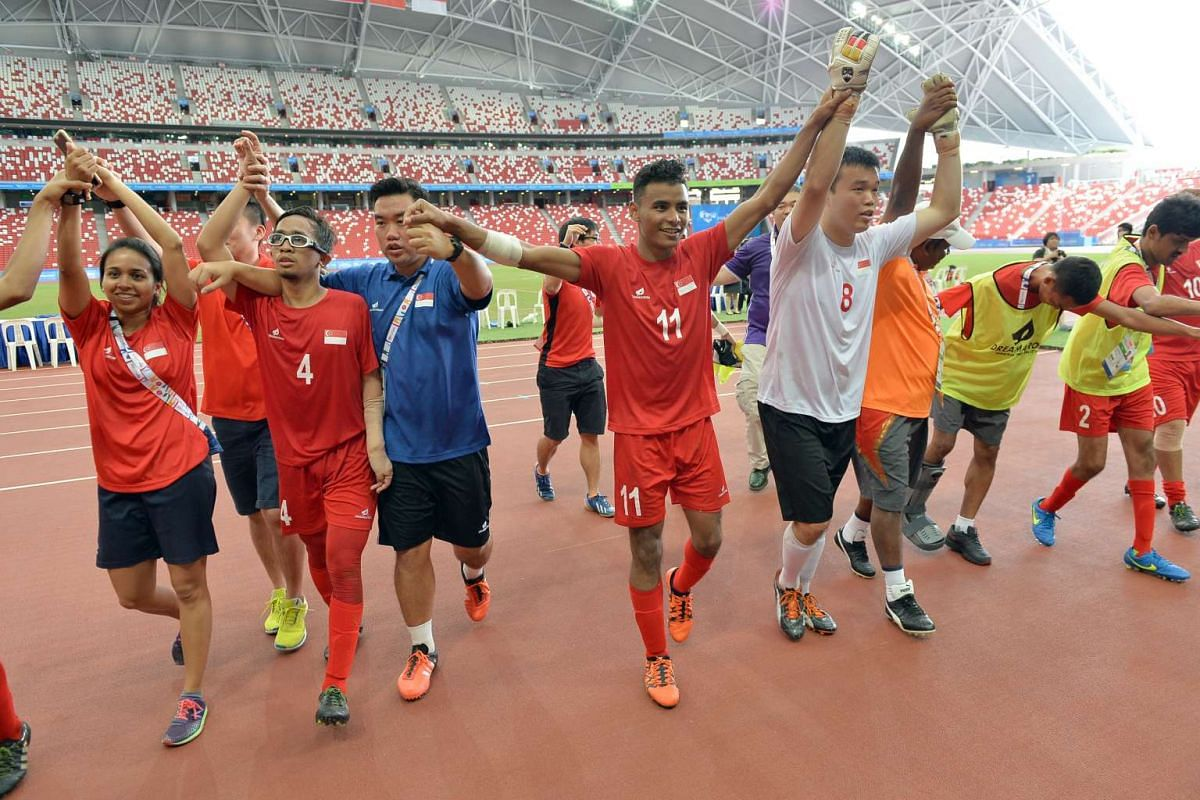 The Singapore cerebral palsy football team celebrates after winning the bronze medal.