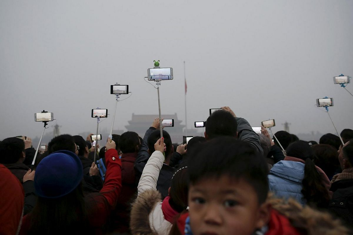 """People filming with their cameras during a flag-raising ceremony amid heavy smog at the Tiananmen Square, after the city issued its first ever """"red alert"""" for air pollution, in Beijing on Dec 9, 2015."""