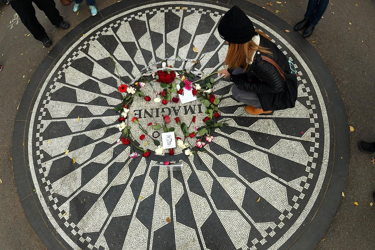 A woman placing a stalk of flower at the mosaic named after John Lennon's song Imagine, at Strawberry Fields, the Central Park garden dedicated in his honour, on Dec 8, 2015,  in New York.