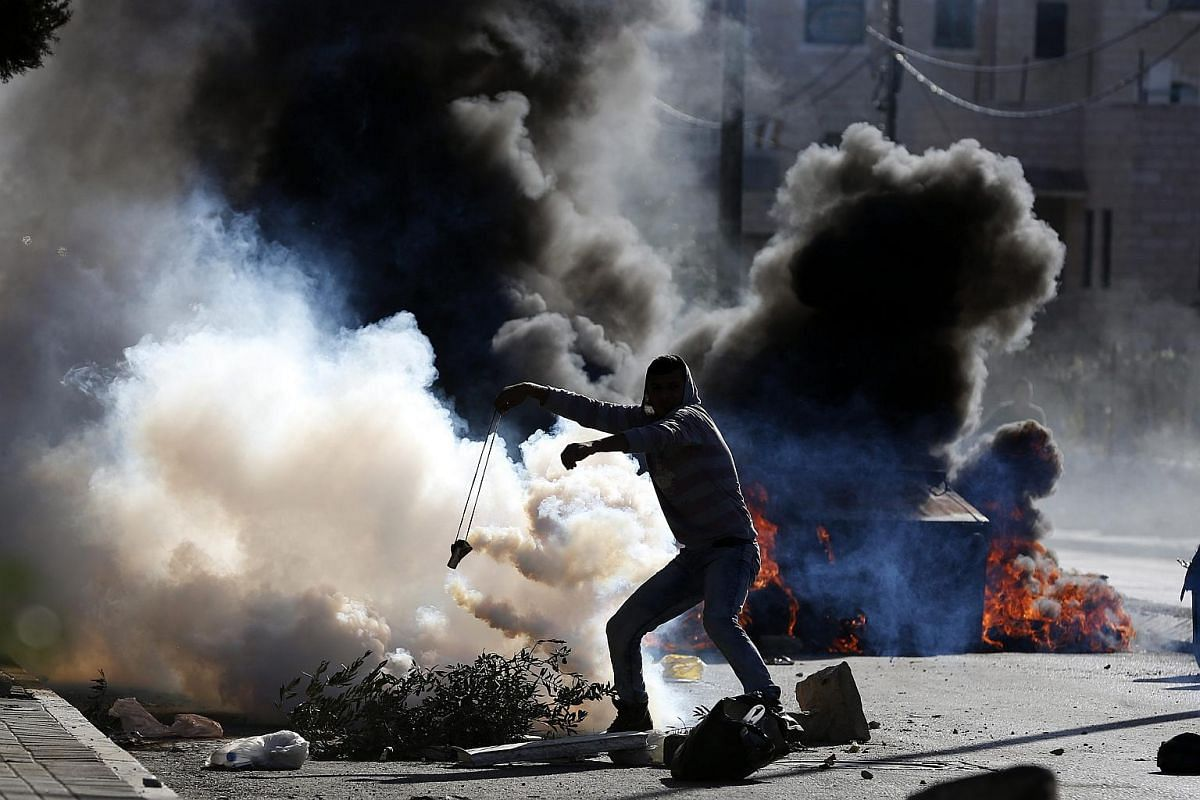 A Palestinian protester throwing a tear gas canister during clashes with Israeli troops in the outskirts of the West Bank city of Bethlehem, on Dec 8, 2015.