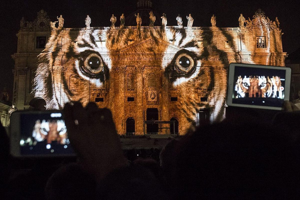 Visitors taking pictures of the Saint Peter's Basilica facade which was illuminated as part of a contemporary public art projection titled Fiat Lux: Illuminating Our Common Home, on the opening day of the Extraordinary Jubilee Of Mercy, in Rome, Ital