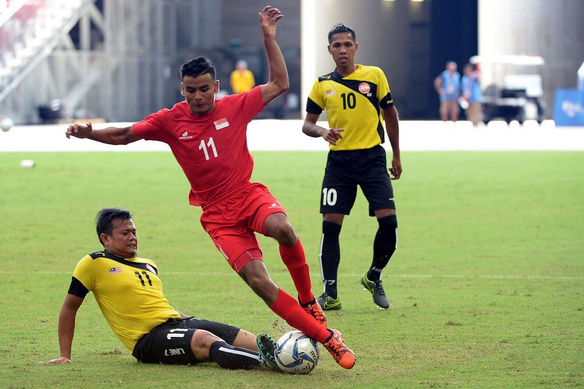 Singapore's #11 Muhammad Mubarak (centre), who scored 2 goals to beat Malaysia and clinch the bronze medal on Dec 7, 2015.