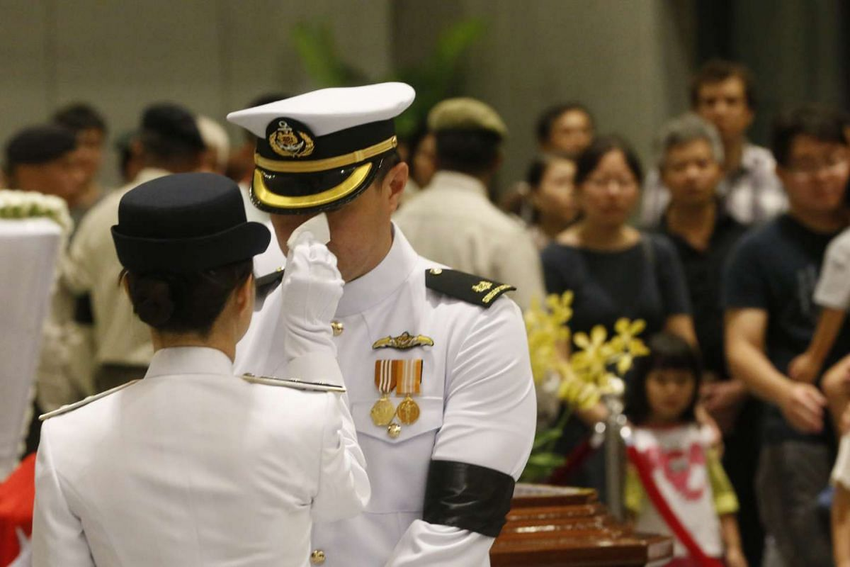 A vigil orderly helping to wipe the perspiration off a vigil guard standing on duty during the funeral of the late Mr Lee Kuan Yew.