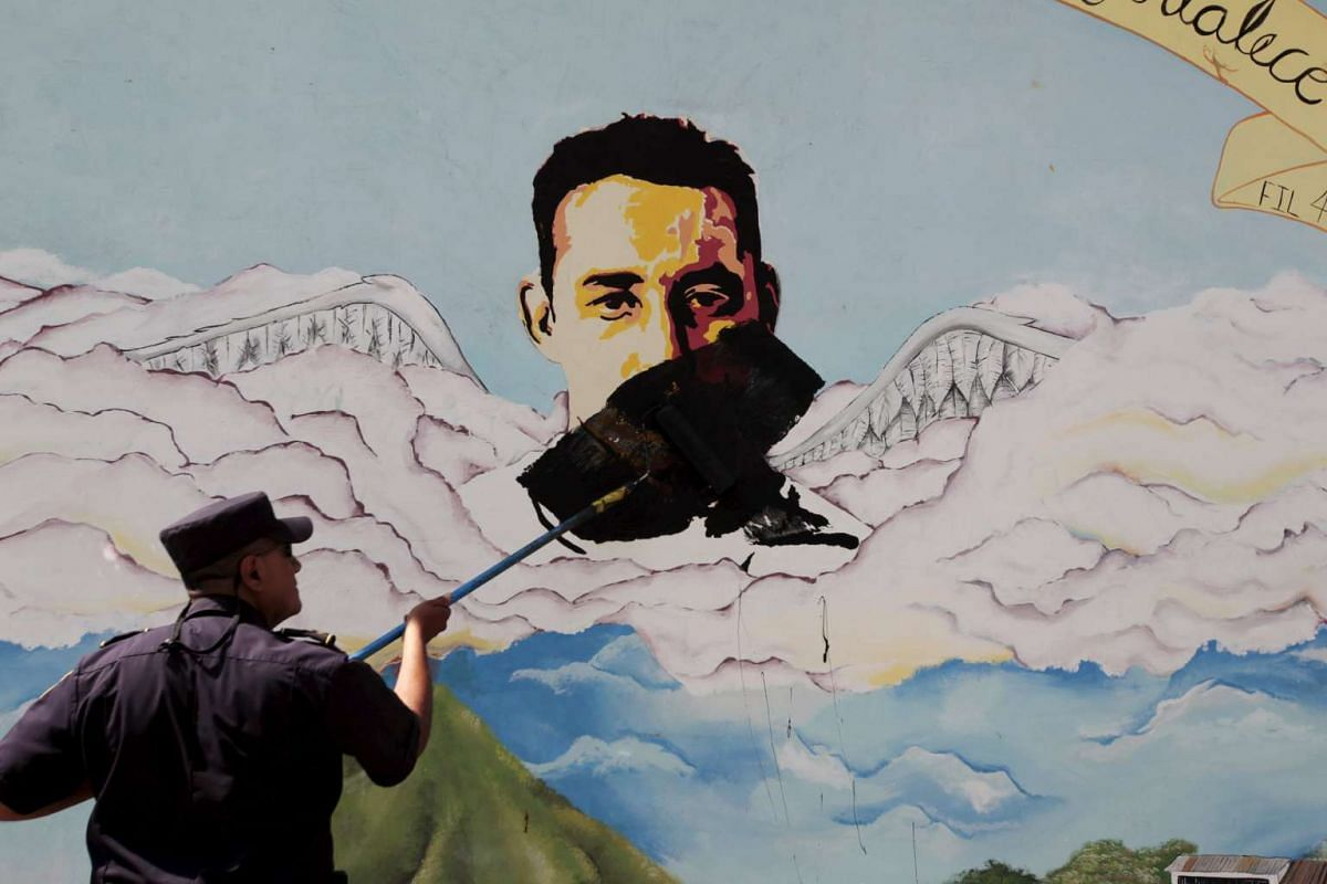 A police officer paints over a graffiti associated with the Mara Salvatrucha gang in the Montreal neighborhood in Mejicanos, El Salvador on Dec 9, 2015.