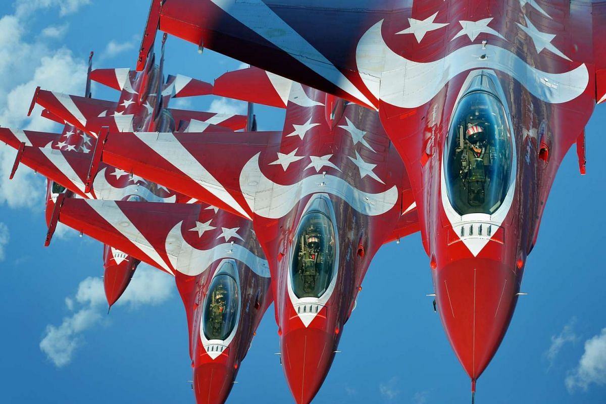 Six F-16C Fighting Falcons of the Republic of Singapore Air Force Black Knights display their topside red-and-white livery during a photo shoot over the South China Sea on Aug 1, 2015.