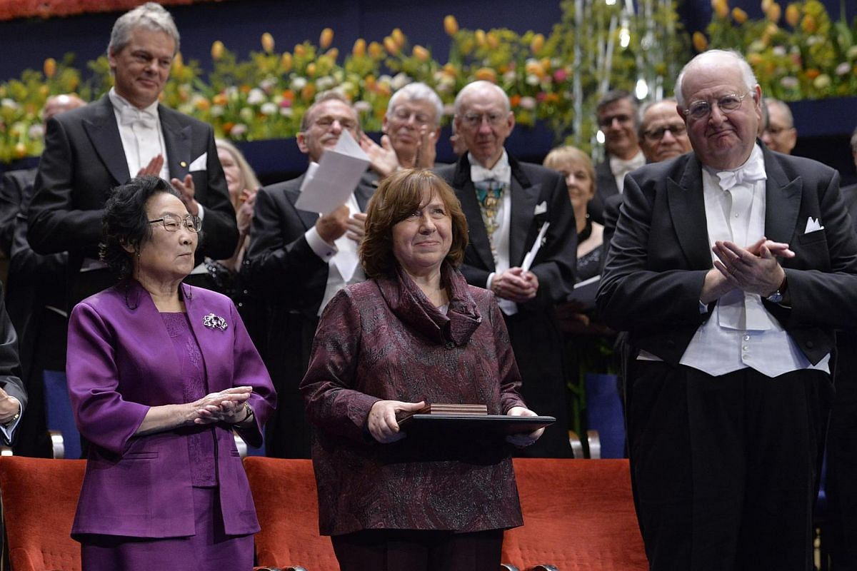 Nobel Prize in Literature 2015 laureate, Belarusian writer and journalist Svetlana Alexievich (centre) is applauded by fellow laureates, Chinese medical scientist Tu Youyou (left) and Scottish-born US economist Angus Deaton (right), after receiving t
