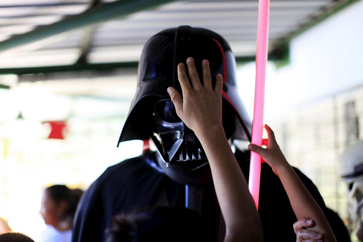 Blind children touching a cosplayer dressed as Darth Vader during a charity event organised by Star Wars fans in El Salvador on Dec 10.