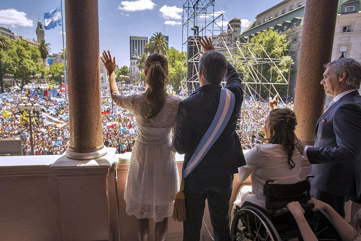 Argentine President Mauricio Macri (centre) and his wife Juliana Awada (left) next to Vice-President Gabriela Michetti, waving at supporters from a balcony of the Casa Rosada government palace in Buenos Aires on Dec 10.