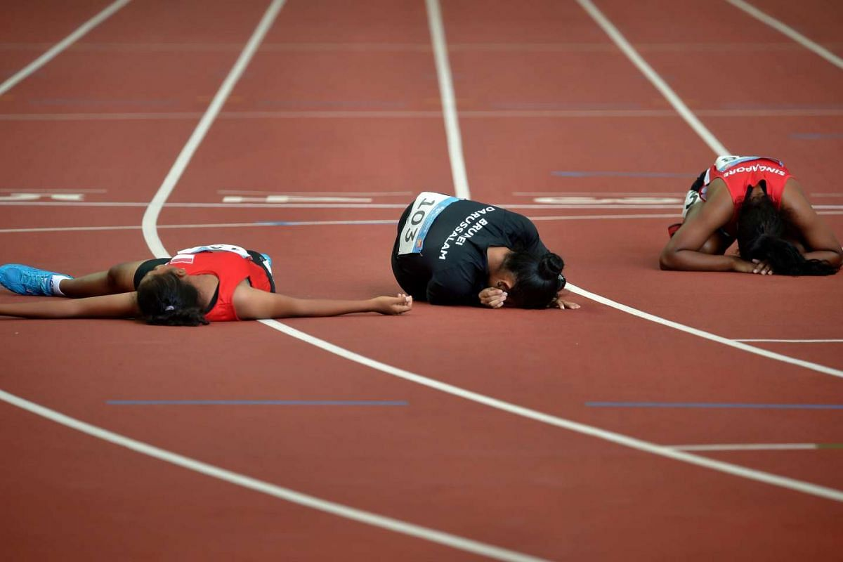 (From left) Indonesia's Septiningtyas Waldani, Brunei's Norsahkinah Sikin and Singapore's Michelle Yogasweri Krishnamoorthy lie exhausted after the women's 400m T20 event, won by Malaysia's Siti Nooriasah Mohamad Ariffin.