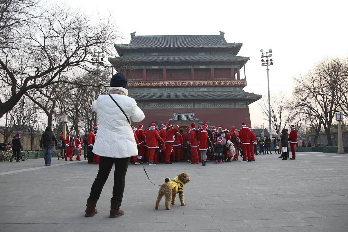 A resident walking her dog looks at participants dressed in Santa Claus costumes near the Drum Tower during the SantaCon in Beijing, China, on Dec 12, 2015. Dozens of people participated in the SantaCon in Beijing on Saturday to celebrate the upcomin