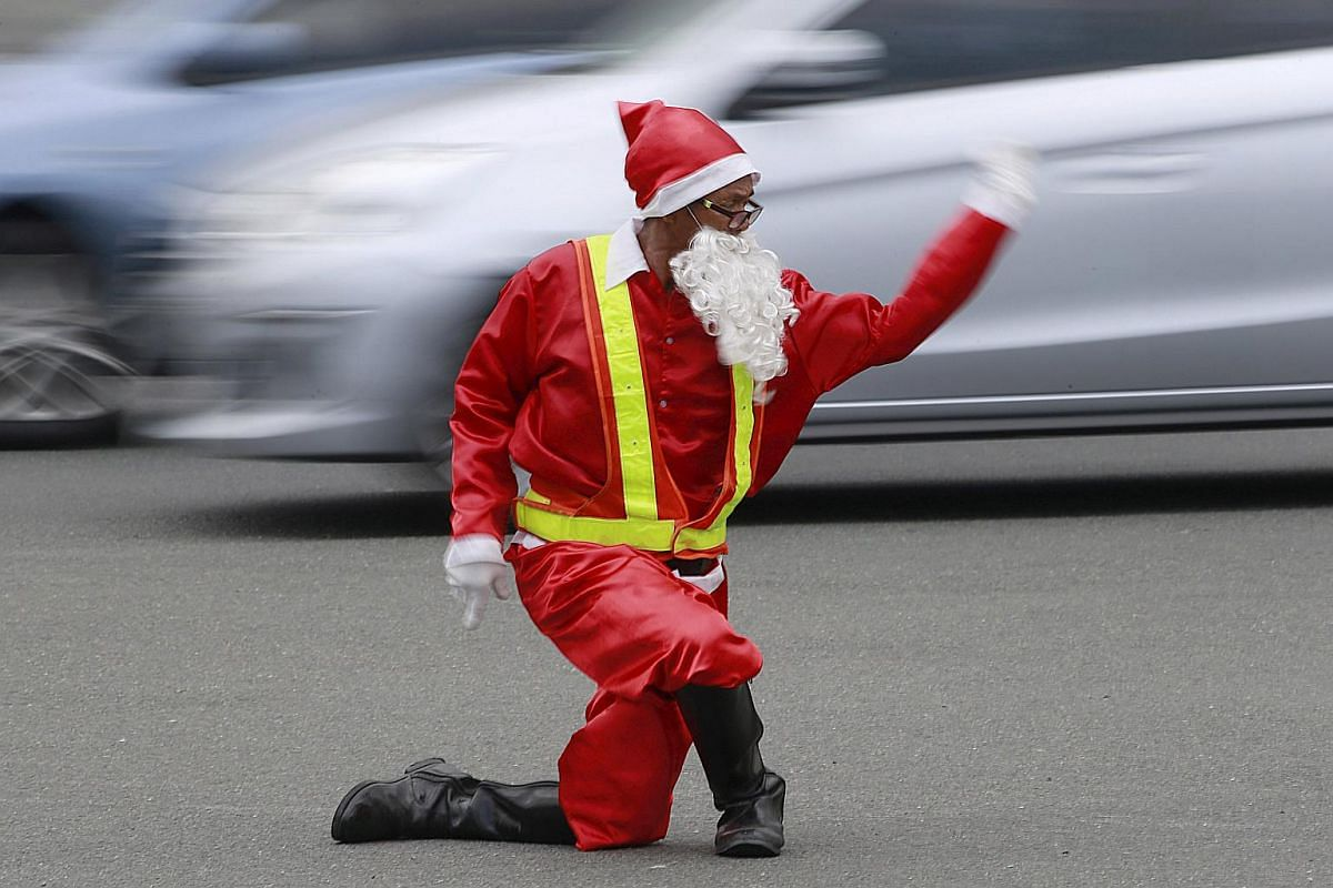 Traffic enforcer Ramiro Hinojas wears a Santa Claus costume while directing traffic flow at a busy intersection in Pasay city, metro Manila, on Dec 12, 2015. Hinojas busts some dance moves while directing traffic to entertain motorists stuck in the c