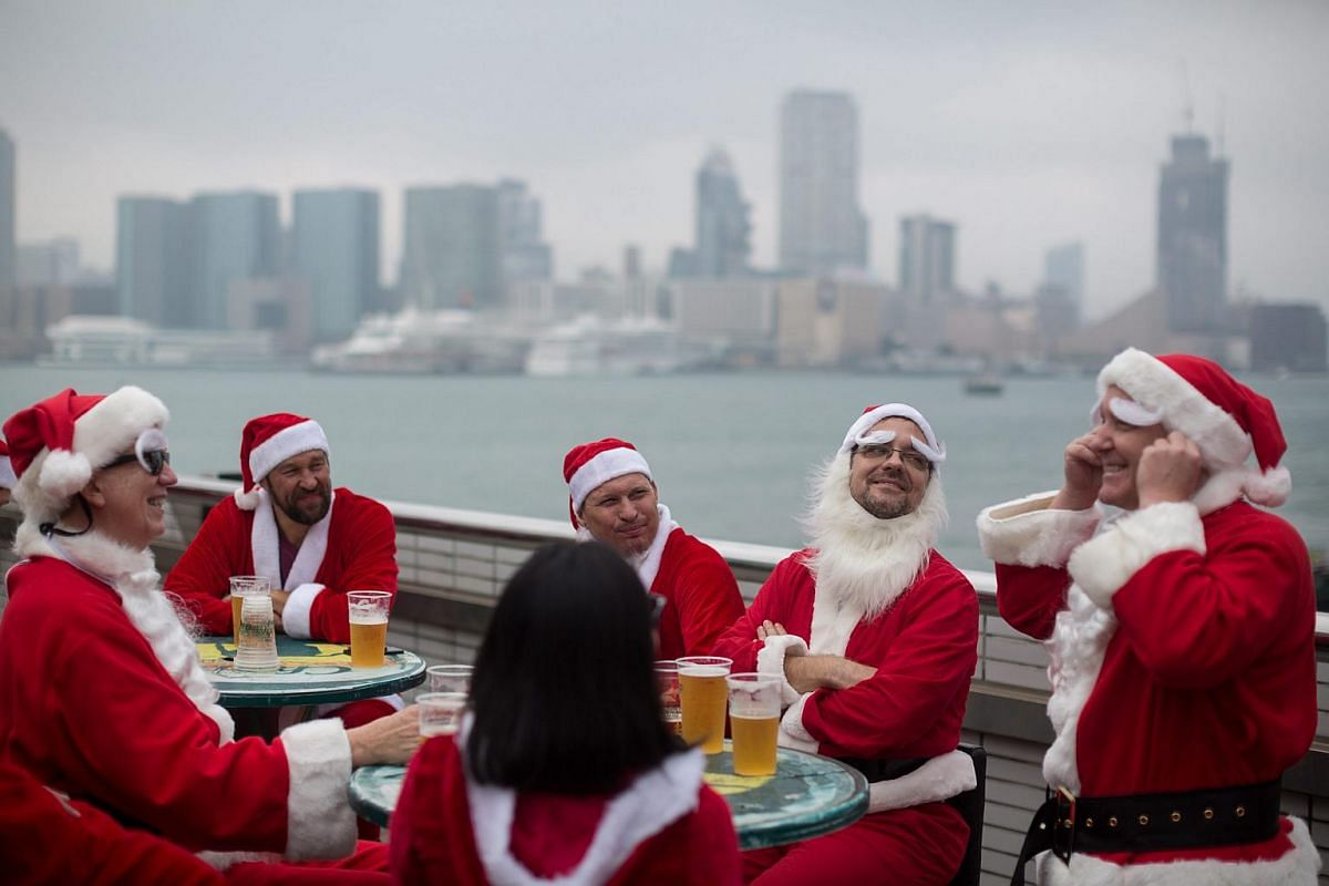 Revellers dressed as Santa Claus drink in a bar during a SantaCon event in Hong Kong on Dec 12, 2015. SantaCon is an annual group gathering and pub crawl in which people dressed in Santa Claus costumes or as other Christmas characters parade in sever