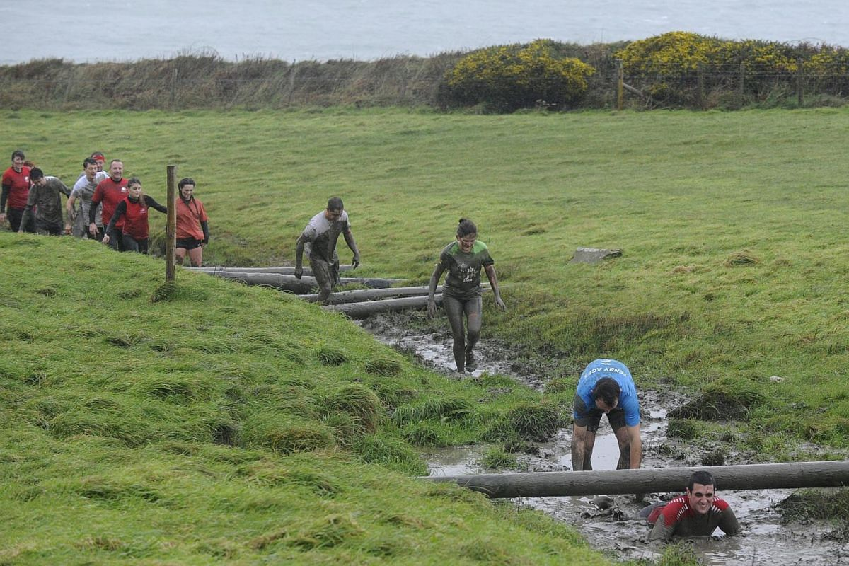Competitors take part in the Christmas Really Wild Mud Run on a 4.6 miles course across undulating farm land at Celtic Camping, St David's, Pembrokeshire, Wales, Dec 12, 2015.