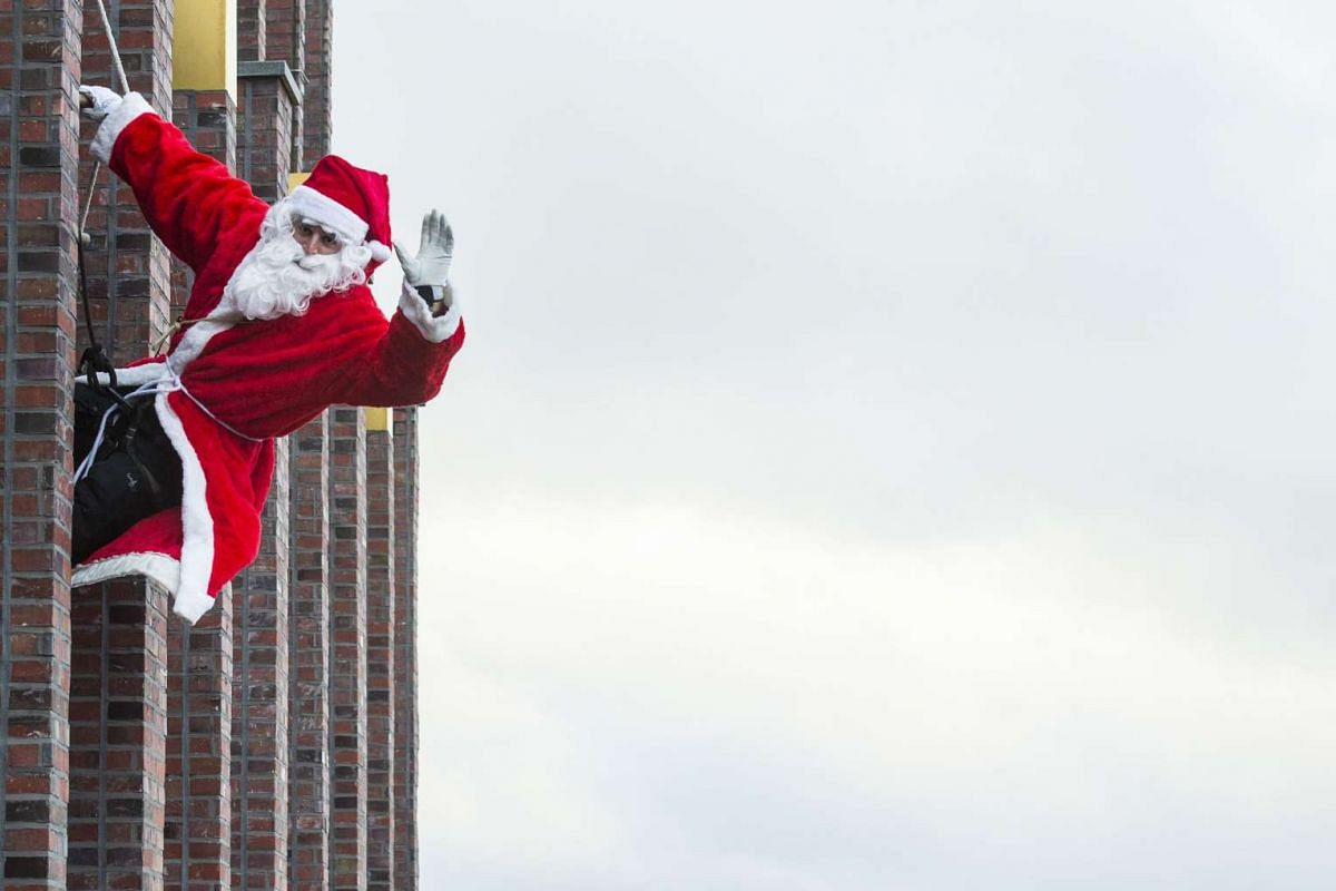 A man dressed as Father Christmas aka Santa Claus climbs down the Kollhoff tower on Dec 13, 2015 as part of a yearly stunt before the festive season.