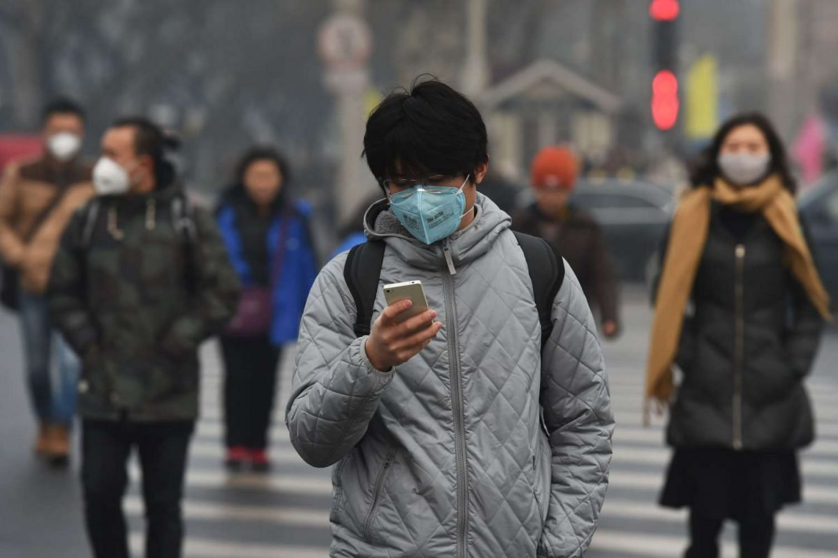 A man checks his smartphone on a polluted day in Beijing on Dec 14, 2015.