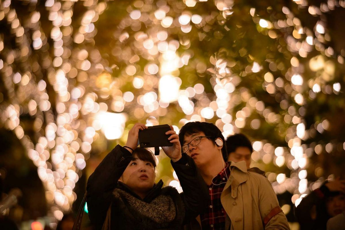 People take photographs using a smartphone in front of a tree decorated with illuminated Christmas lights at night in Tokyo, Japan, on Dec 5, 2015.