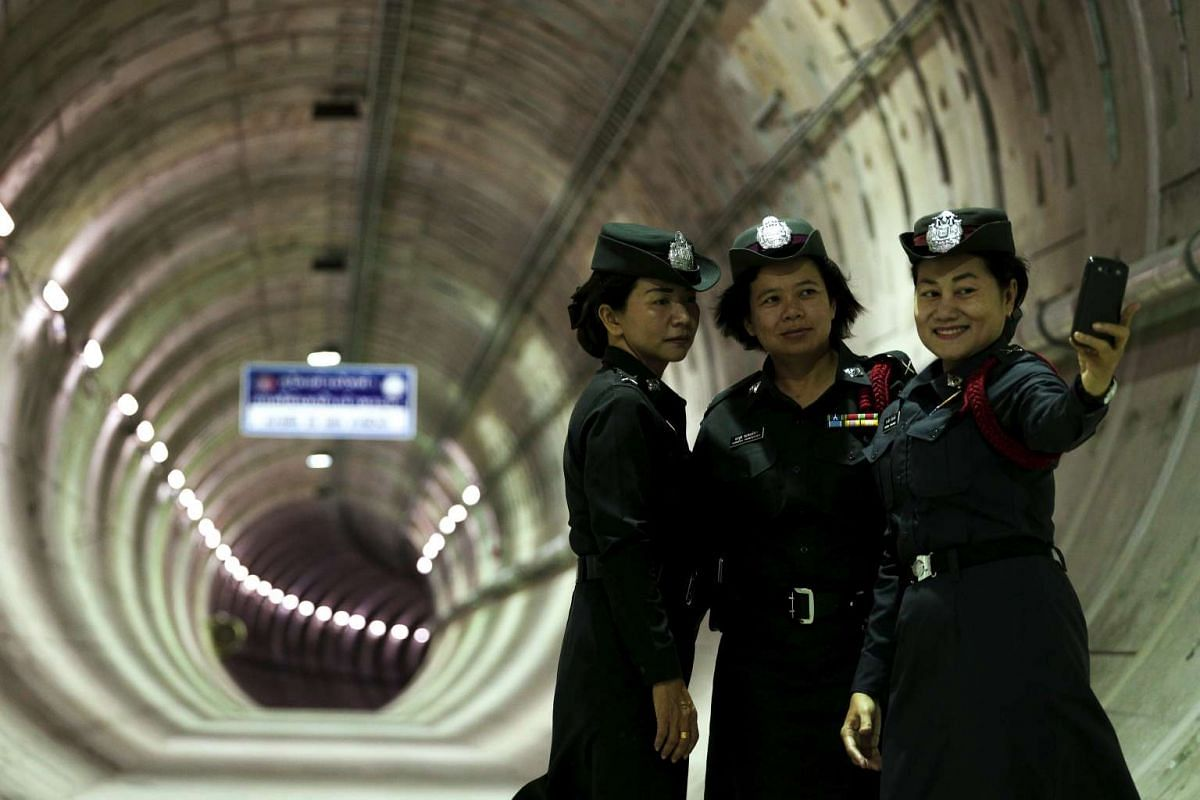 Policewomen take a picture inside a tunnel under the Chao Phraya river at a Mass Rapid Transit subway station in Bangkok, Thailand on Dec 14, 2015.