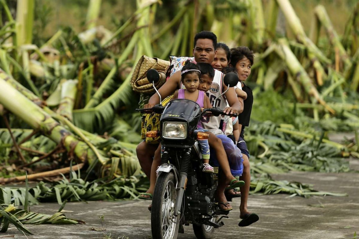 Filipino evacuees ride on a motorcycle as they maneuver among debris in the typhoon hit town of Juban, Sorsogon province, southern Manila, Philippines, 15 December 2015. PHOTO: EPA