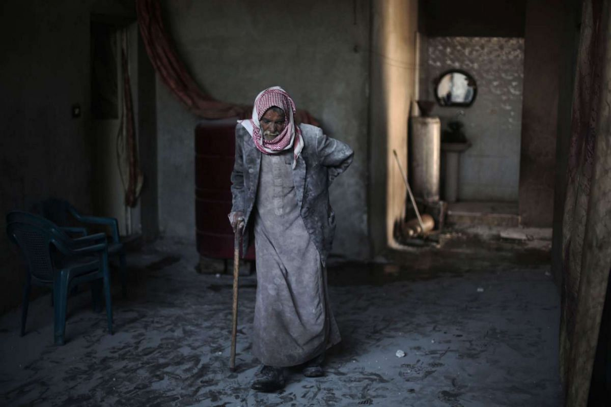 Syrian Abu Mohammed, covered with dust from explosions, walks in his home following reported air strikes by regime forces on the town of al-Nashabiyah in the eastern Ghouta region, a rebel stronghold east of the capital Damascus, on December 14, 2015