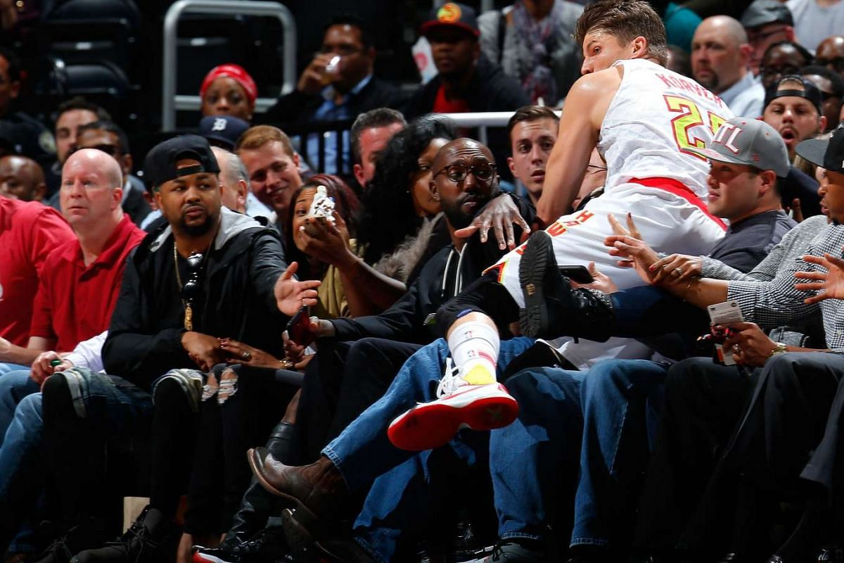 Kyle Korver #26 of the Atlanta Hawks lands in the first row after saving a loose ball against the Miami Heat at Philips Arena on December 14, 2015 in Atlanta, Georgia.  PHOTO: GETTY IMAGES/AFP
