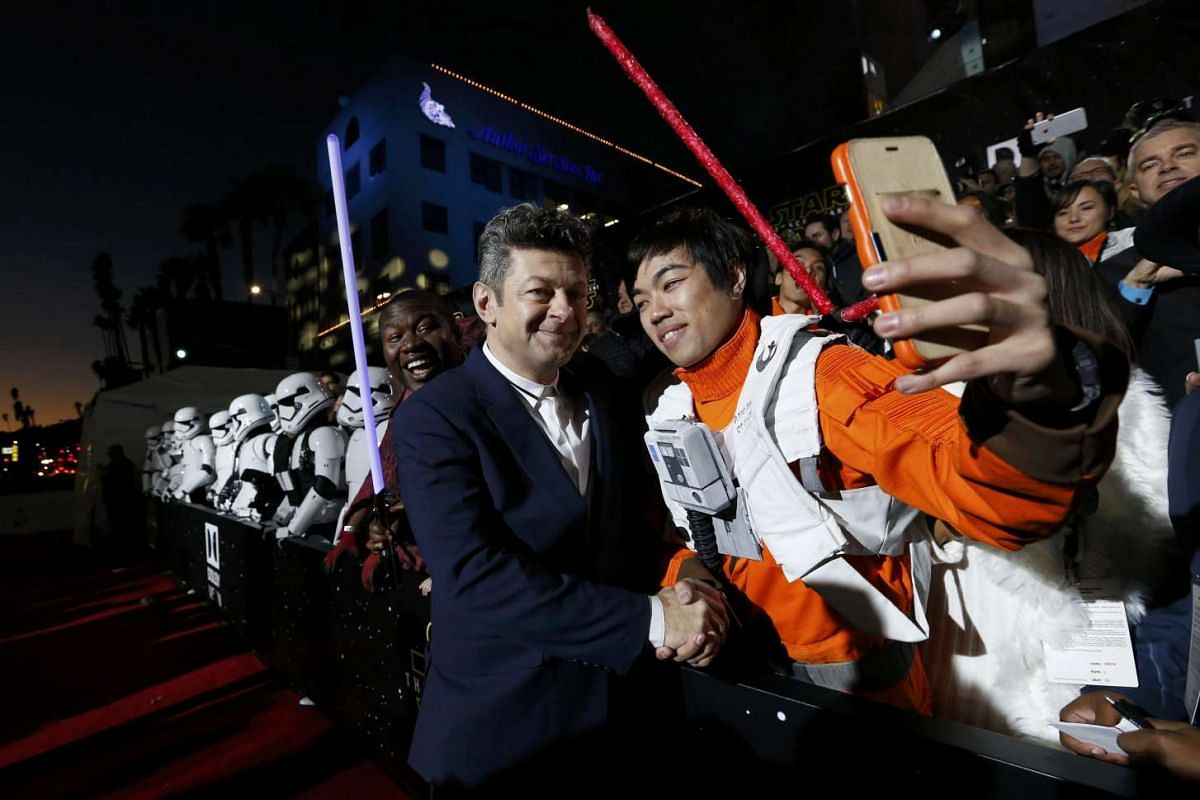 Actor Andy Serkis (left) posing with fans as he arrives at the premiere of Star Wars: The Force Awakens.