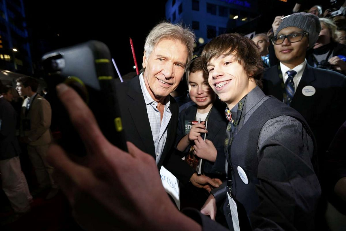 Actor Harrison Ford (left) posing for a selfie with a fan as he arrives at the premiere of Star Wars: The Force Awakens.
