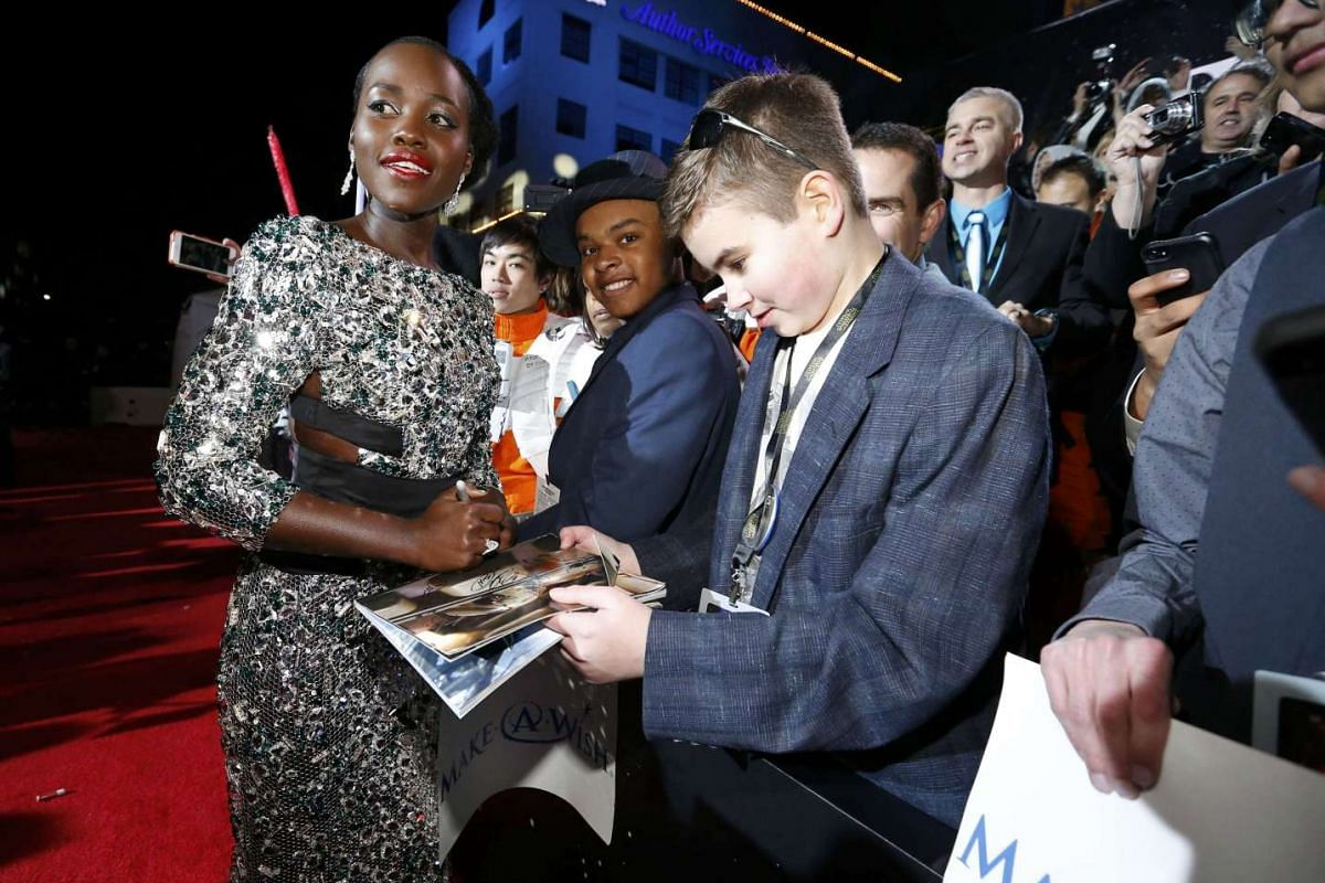 Actress Lupita Nyong'o signing an autograph for a fan as she arrives at the premiere of Star Wars: The Force Awakens.