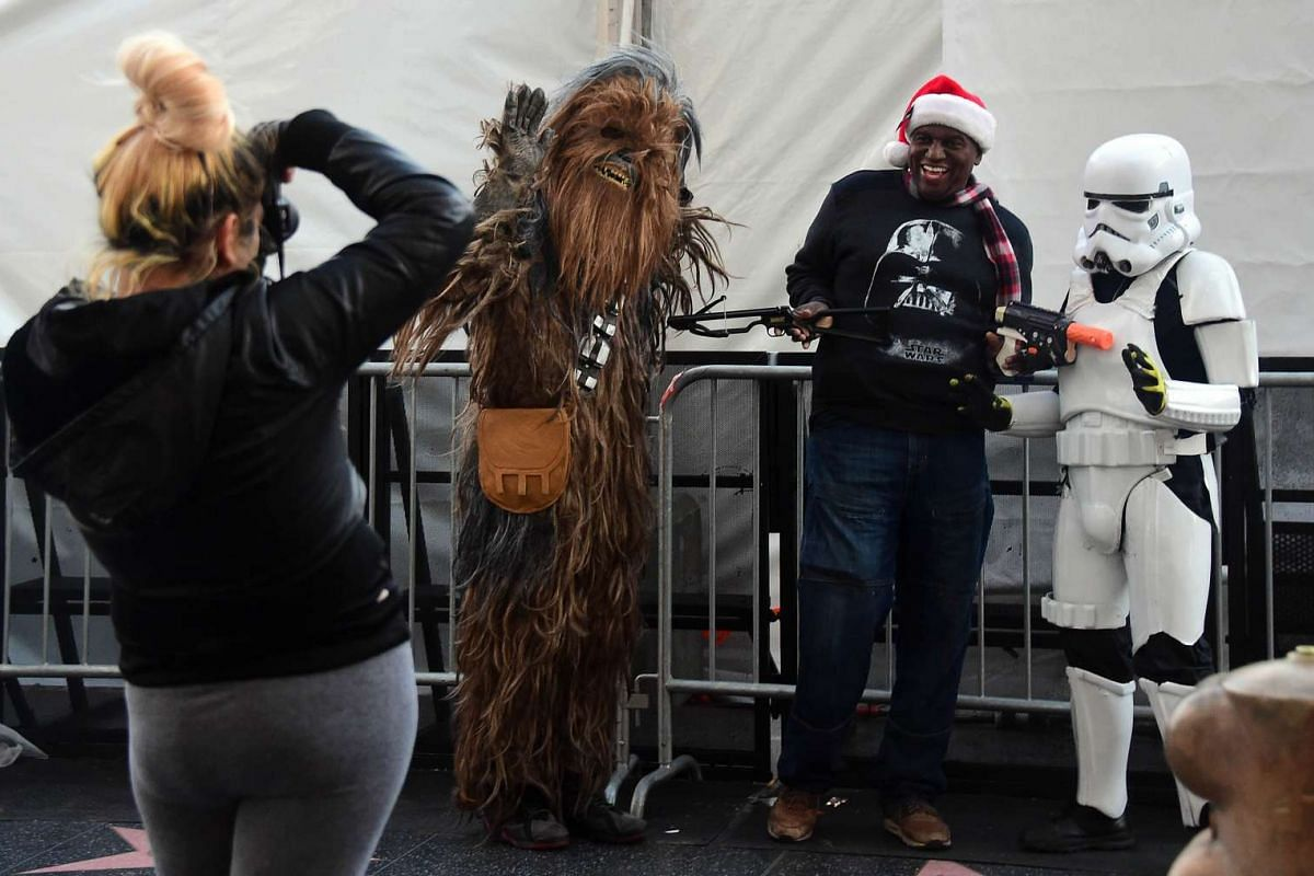 Star Wars fans dressed as Chewbacca and a Stormtrooper posing for a photo with a man in a Santa hat along Hollywood Boulevard in Hollywood, California on Dec 14, 2015, in front of the large white tent lining the street for the premiere of the latest