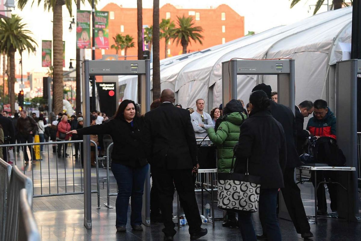 People going through security check point beside a large white tent lining Hollywood Boulevard for the premiere of the latest Star Wars film, The Force Awakens, in Hollywood, California on Dec 14, 2015.