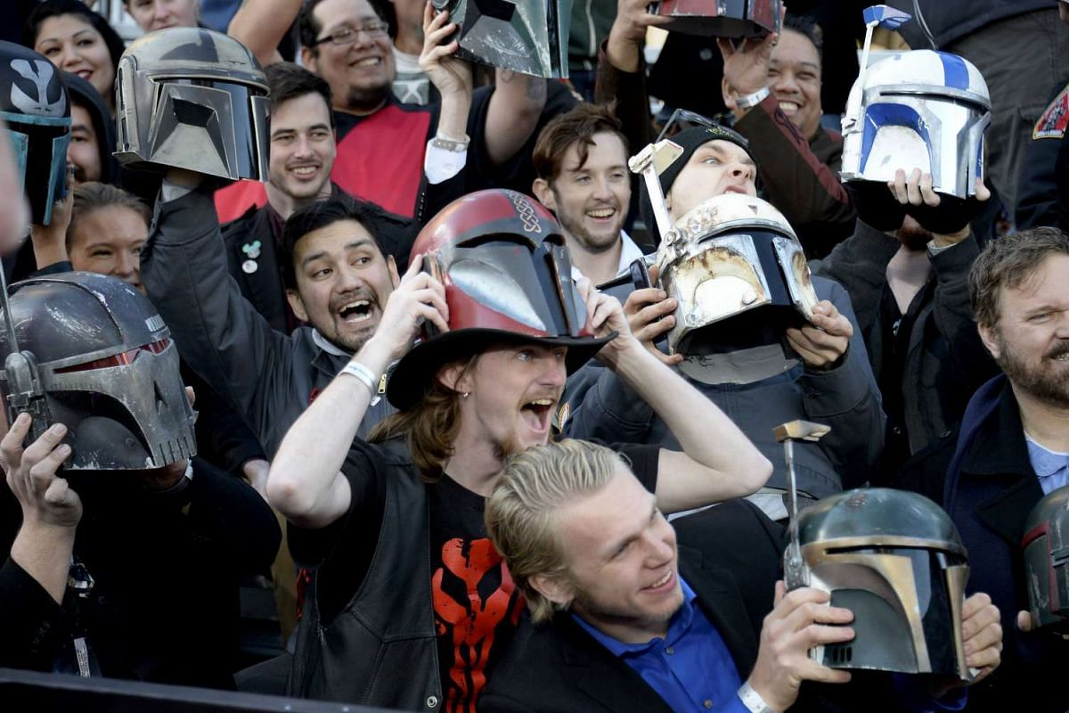 Fans holding up helmets at the premiere of Star Wars: The Force Awakens in Hollywood, California, on Dec 14, 2015.
