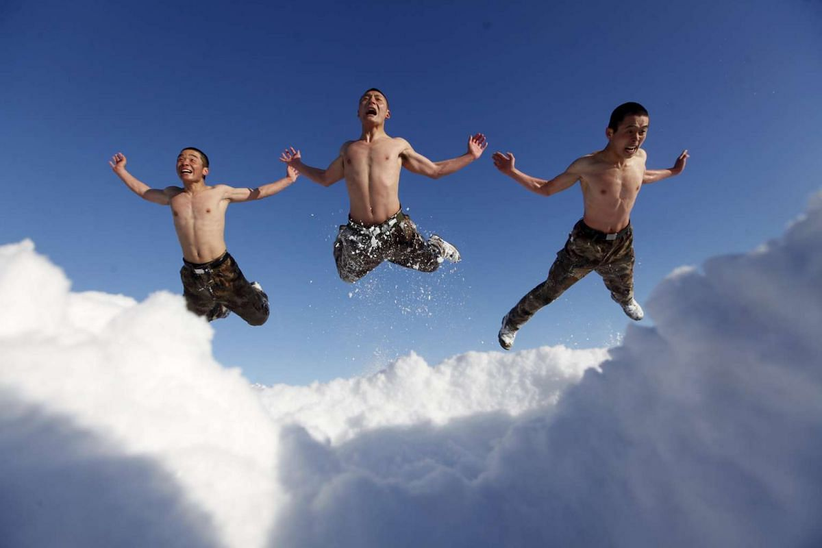 In this photo made available on December 16, 2015, soldiers of China's People's Liberation Army (PLA) jump as part of their winter training in temperature of negative 26 degrees Celsius at China's border with Russia in Heihe, Heilongjiang province, D