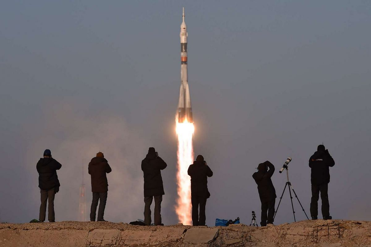 Photographers take pictures as Russia's Soyuz TMA-19M spacecraft carrying the International Space Station (ISS) Expedition 46/47 crew, blast off from the launch pad at Russian-leased Baikonur cosmodrome on December 15, 2015. PHOTO: AFP