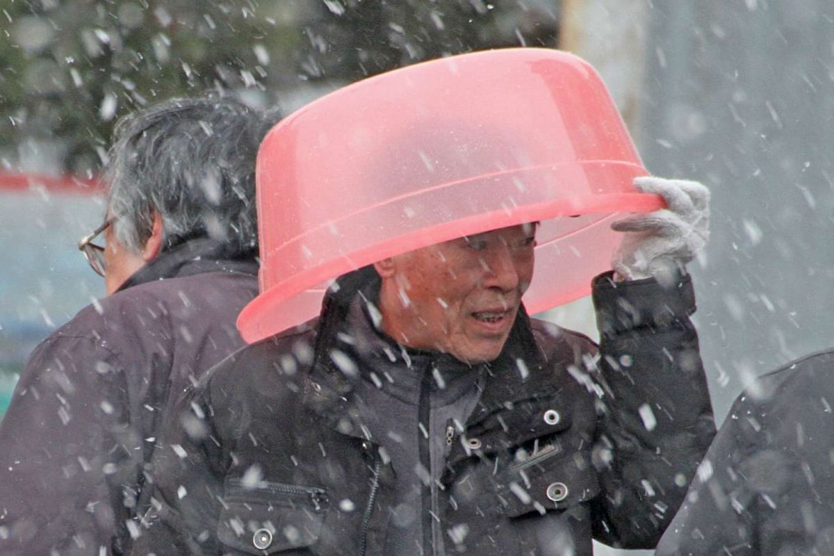 A man covers his head with a basin during snowfall in Yantai, Shandong province, December 16, 2015. PHOTO: REUTERS/CHINA STRINGER NETWORK