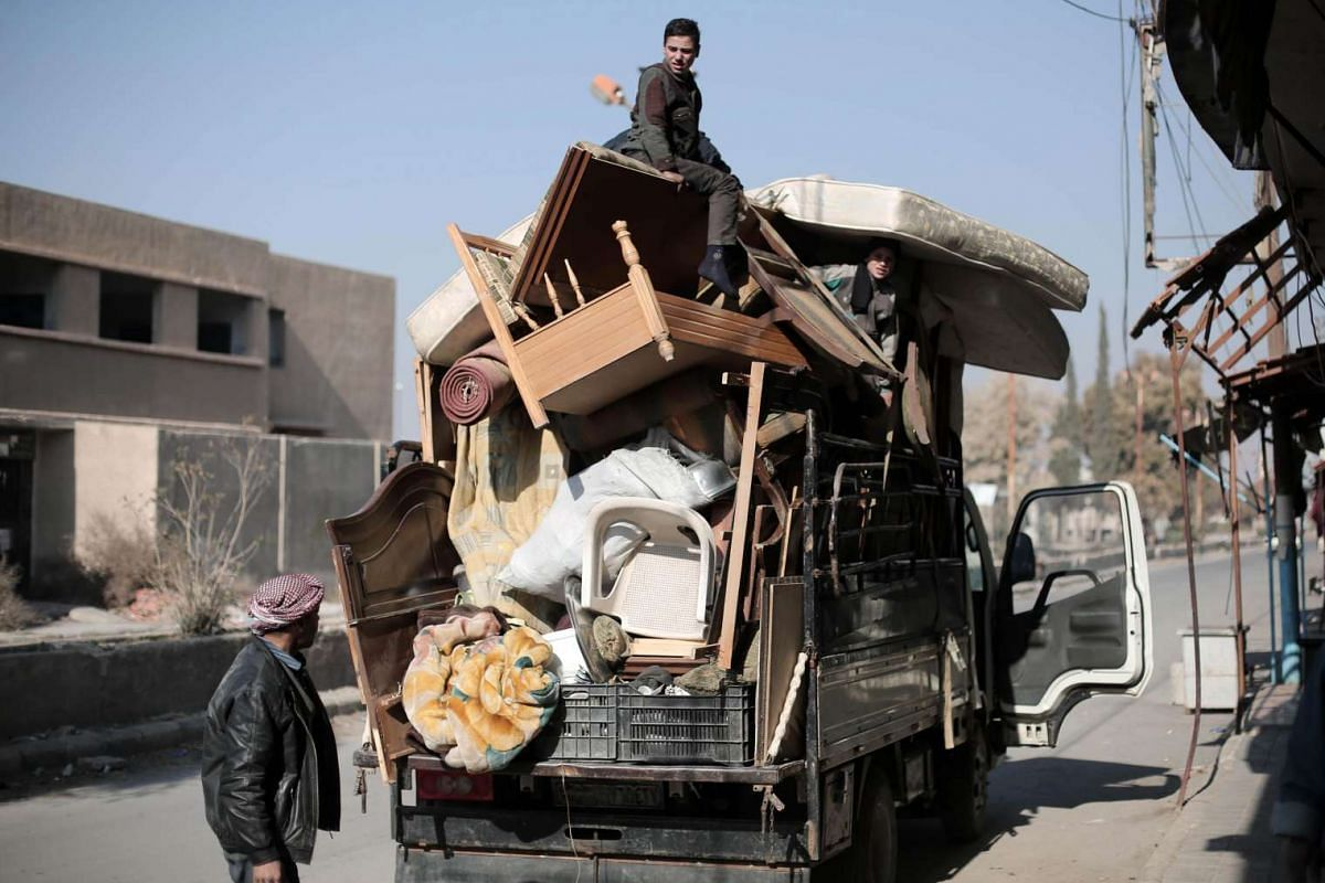 Syrians leave with their belongings, away from the town of al-Nashabiyah in the eastern Ghouta region, a rebel stronghold east of the capital Damascus, following the government forces' advance around Eastern Ghouta on December 15, 2015. PHOTO: AFP