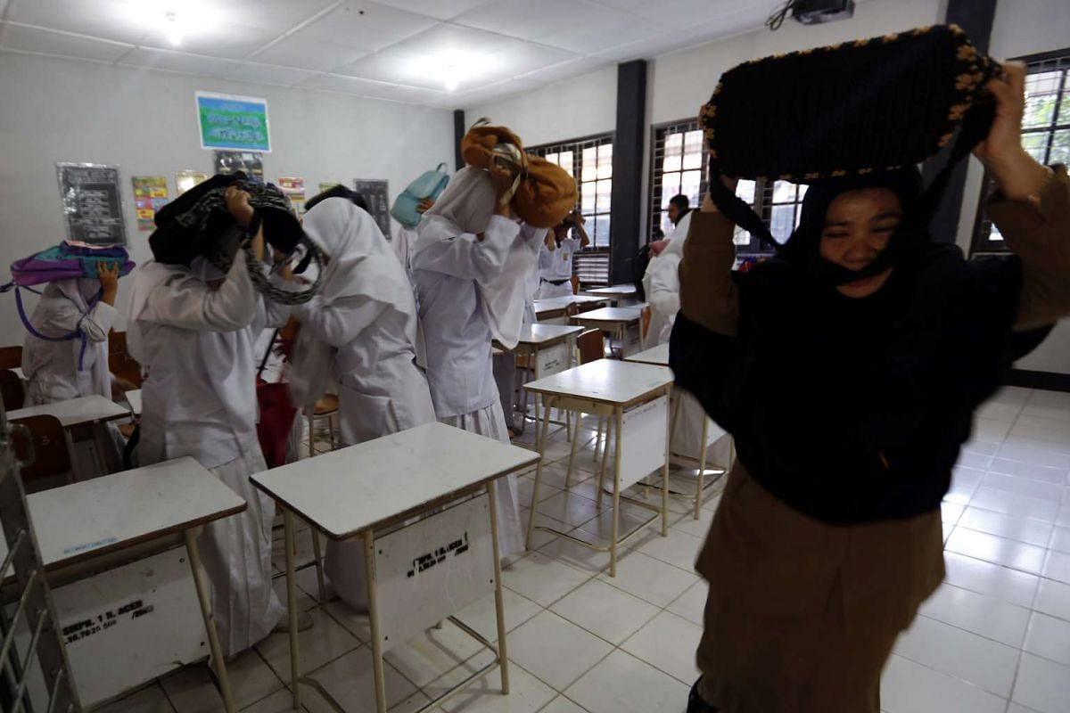Students and teachers try to escape from a classroom by covering their heads with bags during a tsunami drill as part of a disaster awareness program at a school in Banda Aceh, Indonesia, 17 December 2015. PHOTO: EPA